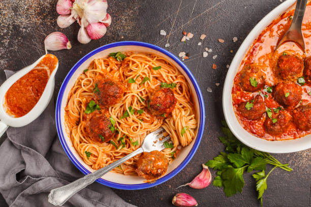 Pasta with meatballs in tomato sauce with parsley and garlic in white dish, top view, dark background. stock photo