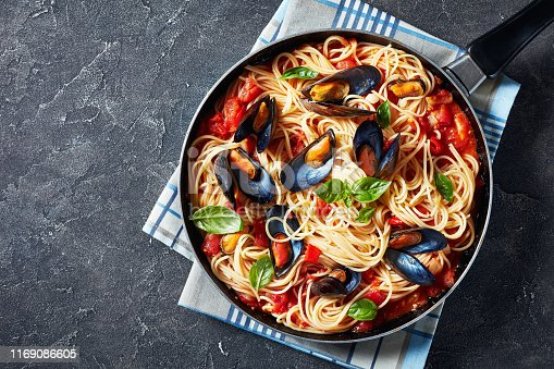 spaghetti with Mussels in a Spicy Tomato Sauce in a skillet on a concrete table, horizontal view from above, flatlay, empty space