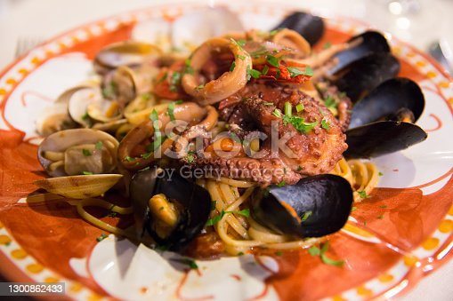 Italian food: seafood spagetti with grilled octopus and mussels on a hand-painted ceramic plate of the island of Capri, Tyrrhenian sea, Italy
