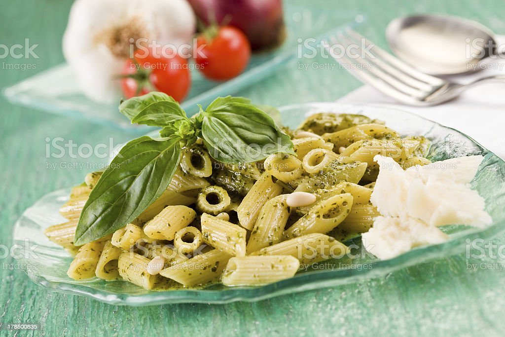 Pasta with pesto on green glass table stock photo