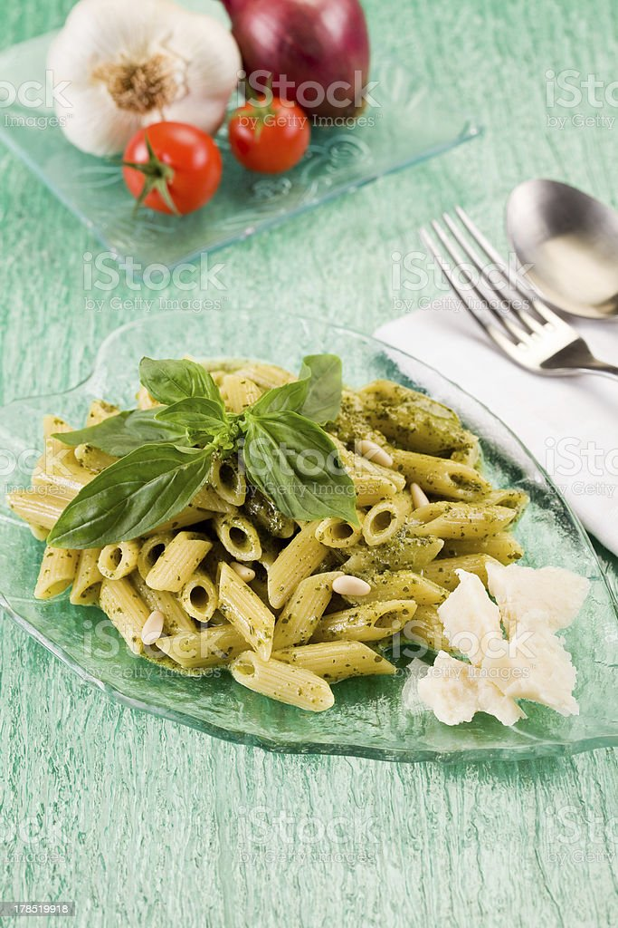 Pasta with pesto on green glass table royalty-free stock photo