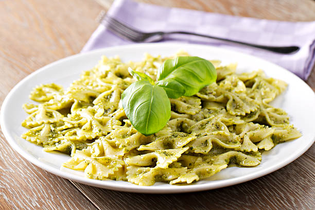 Pasta with pesto sauce Pasta with pesto sauce. bow tie pasta stock pictures, royalty-free photos & images