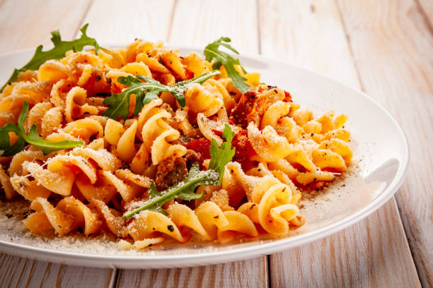 Pasta with pork, sauce and vegetables on color gradient background Fusilli with pork, sauce and vegetables on color gradient background fusilli stock pictures, royalty-free photos & images