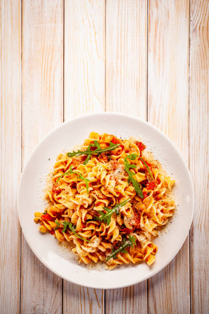 Pasta with pork, sauce and vegetables on color gradient background stock photo