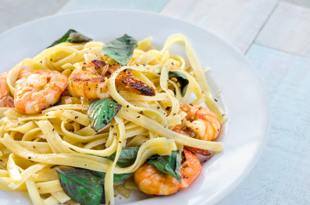 Pasta with prawns and basil leaves stock photo