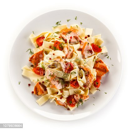 Pasta with salmon and vegetables on white background