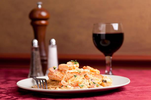 pasta mit lachs, jakobsmuscheln und garnelen - spaghetti mit lachs stock-fotos und bilder