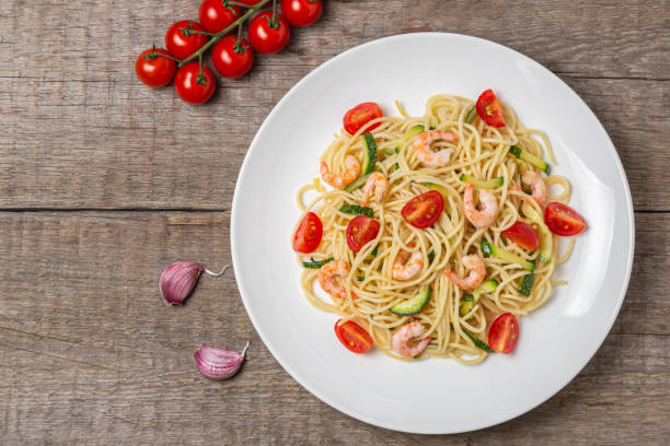 Pasta with shrimp and vegetables. The view from the top. Copy space. Pasta with shrimp, tomatoes and zucchini. Dietary food. cymbal stock pictures, royalty-free photos & images
