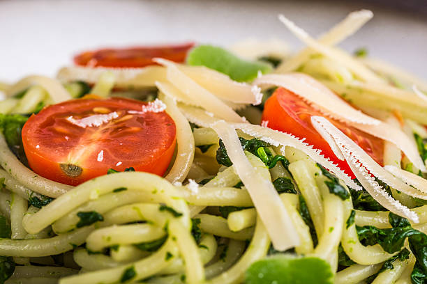 Pasta with spinach, tomatoes and cheese on plate stock photo