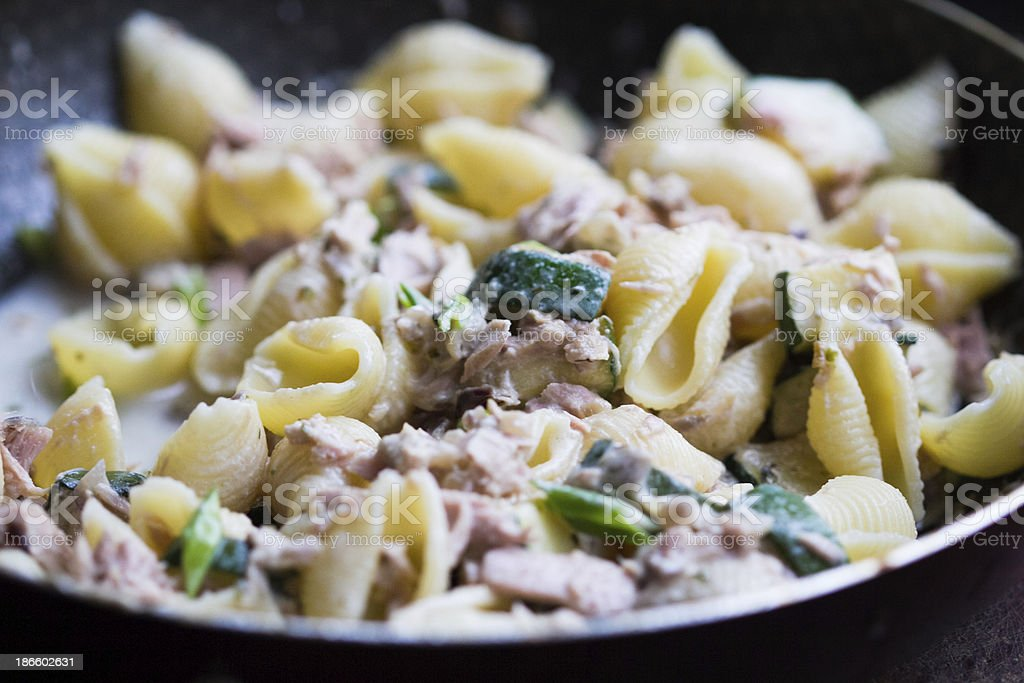 Pasta with tuna, zucchini, sauce and herbs in frying pan stock photo