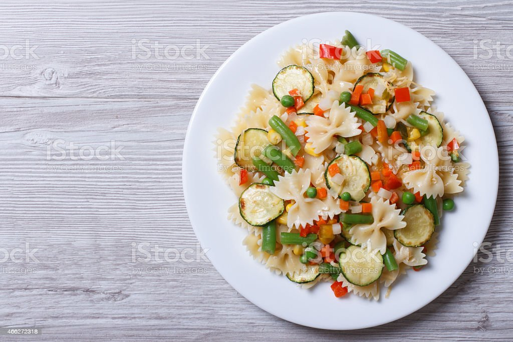 pasta with vegetables on a wooden background. top view stock photo