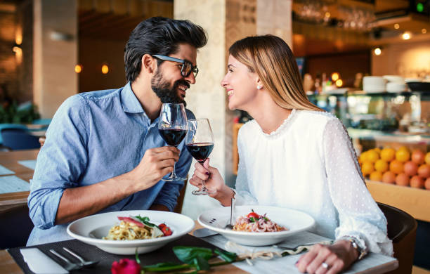 Paste and red wine. Young couple enjoying lunch in the restaurant. Lifestyle, love, relationships, food concept stock photo