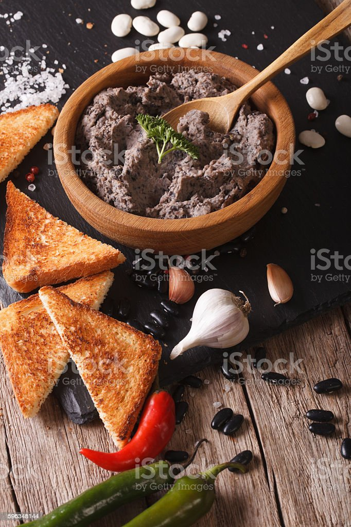 paste of black beans with ingredients close-up. vertical stock photo