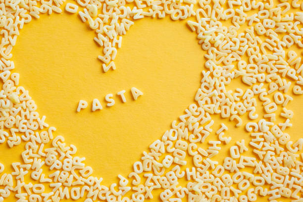 Paste of letters of the alphabet, on a bright yellow background with a heart shape. In the middle of the heart there is an inscription - PASTA stock photo