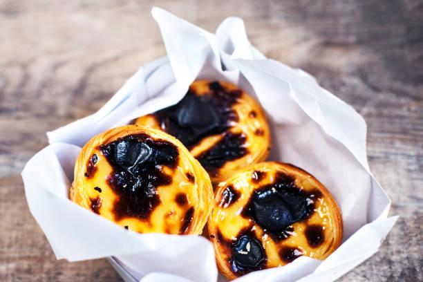 pasteis de nata - cremige ei-tarte mit süßen curstard, kruste und zucker schwarzpulver auf hölzernen hintergrund. pasteis de belem gebäck - portugiesische desserts stock-fotos und bilder
