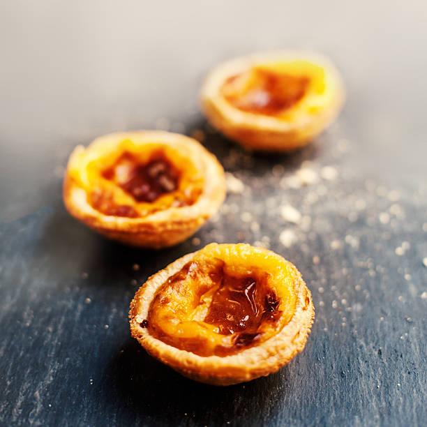 gebäcks pasteis de nata (portugiesisches puddingtörtchen), typisch portugiesischen eiertörtchen servierte auf dunklen backgroun - portugiesische desserts stock-fotos und bilder
