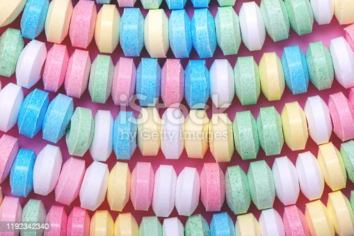Pastel background made of multicolored candy necklace.