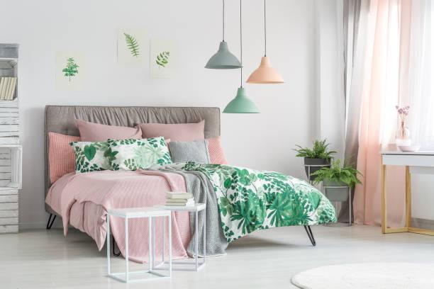 pastellfarbene bettwäsche auf stilvolles bett - schlafzimmer beleuchtung stock-fotos und bilder