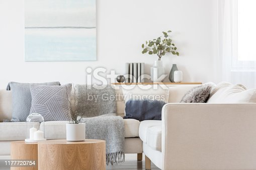 Pastel blue and white abstract oil painting on empty white wall with console table with flowers in vase and books