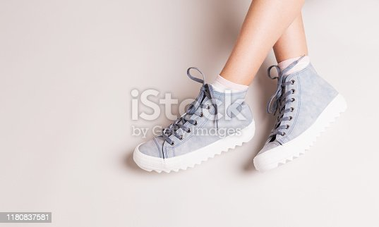 Pastel blue sneakers on crossed legs. Footwear on grey background. Layout with free copy (text) space.