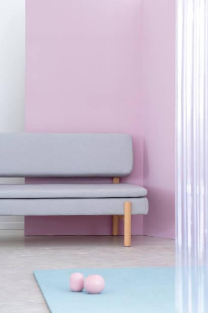 pastellblau polsterbank sofa mit den hölzernen beinen durch ein lavendel-lila wand in ein buntes wohnzimmer interieur. echtes foto. - gepolsterte bank stock-fotos und bilder