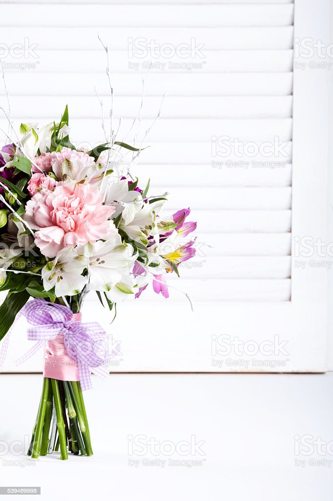 Pastel bouquet from pink and purple gillyflowers on white shutte stock photo
