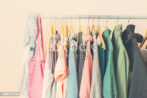Pastel Color Female Clothes in a Row on Open Hanger. Toned image