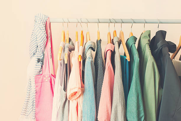 pastel color female clothes in a row on open hanger - garment stock photos and pictures