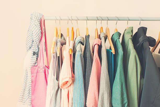 pastell weibliche kleider in einer reihe auf offene kleiderbügel - uhrenhalter stock-fotos und bilder