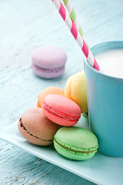 Pastel color macaroons and a cup of milk stock photo