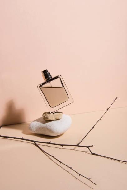 pastelowe kolorowe perfumy spadające z kamienia . abstrakcyjne martwe życie. kolekcja makijażu 5. - perfumowany zdjęcia i obrazy z banku zdjęć