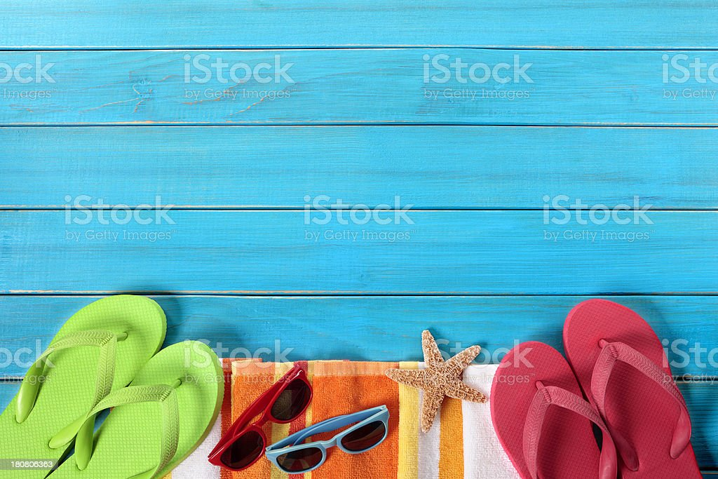 Pastel colored beach gear and starfish on blue boardwalk stock photo