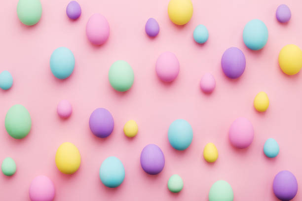 Pastel colored Easter eggs pattern on pink background Pastel colored Easter eggs pattern on pink background. Colorful holiday card Happy Easter. Minimal style, flat lay. saturated color stock pictures, royalty-free photos & images