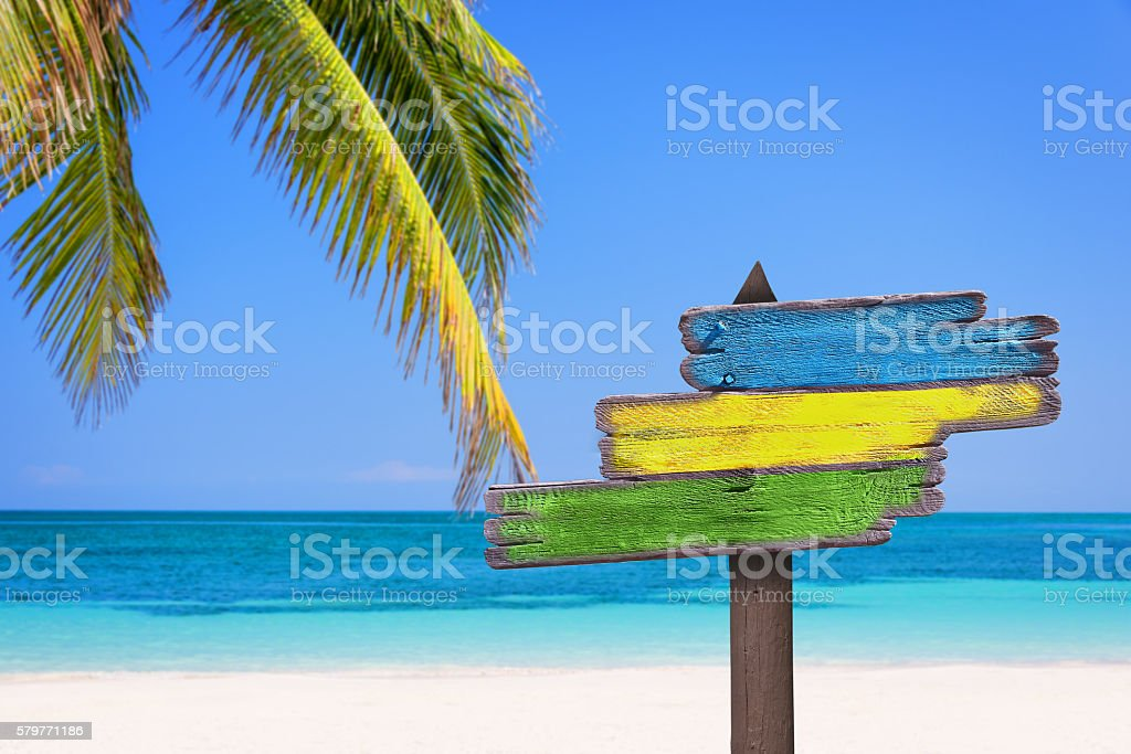 Pastel colored wooden direction signs, beach and palm tree background stock photo