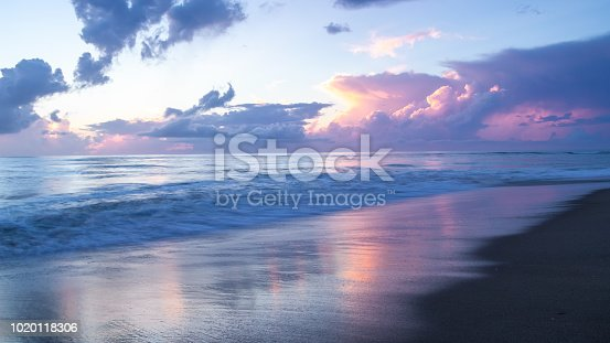A beautiful sunrise filled with shades of pink, magenta and blue. The colors of the sky reflected on the wet sand and smooth surface of the ocean. Long exposure gives a softness and sense of motion.