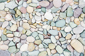 Sea pebbles texture. Nature background with rounded gravel. Top view. Pastel colors
