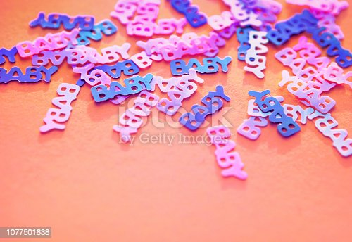 875685464istockphoto Pastel coloured confetti baby on pink background 1077501638