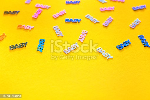 875685464istockphoto Pastel coloured confetti with words baby scattered on yellow background 1073139320