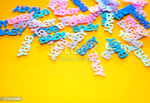 875685464istockphoto Pastel coloured confetti with words baby scattered on yellow background 1073139366