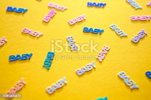 875685464istockphoto Pastel coloured confetti with words baby scattered on yellow background 1081300372