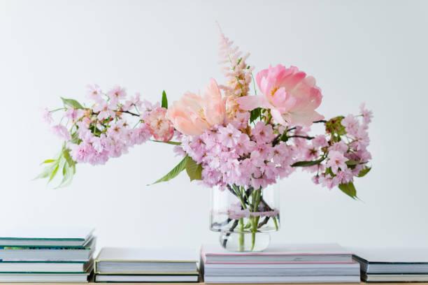 pastell blumen in einer glasvase - bücherbund stock-fotos und bilder