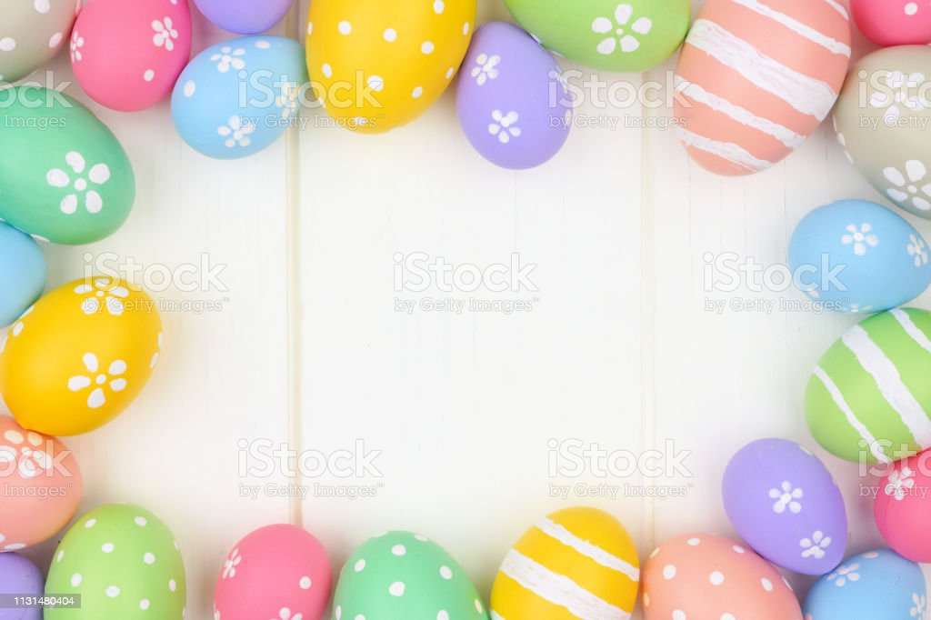 Colorful pastel Easter Egg frame against a white wood background. Top...