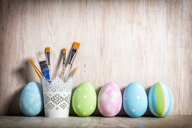 pastell ostereier und bürsten in einer rustikalen tasse - decoupage kunst stock-fotos und bilder