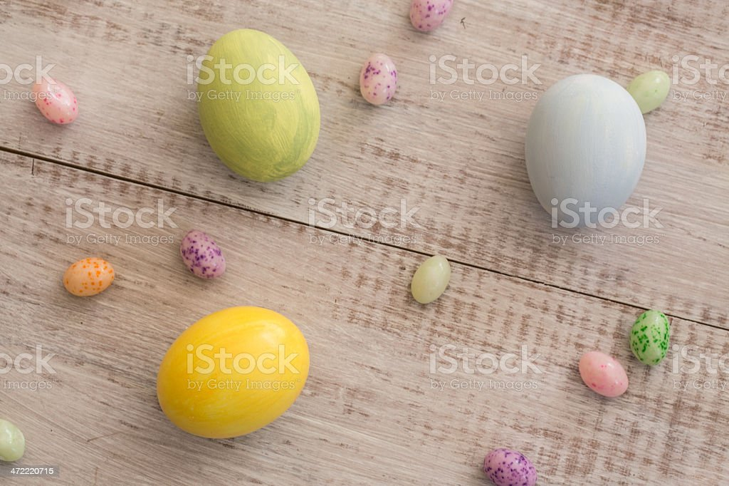 Pastel Easter Eggs and Jelly Beans on White Wood Background stock photo