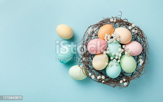1138213028 istock photo Pastel Easter eggs in nest on blue background top view. Flat lay modern minimalistic style. 1210940970