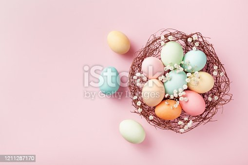 1138213028 istock photo Pastel Easter eggs in nest on pink background top view and flat lay. 1211287170
