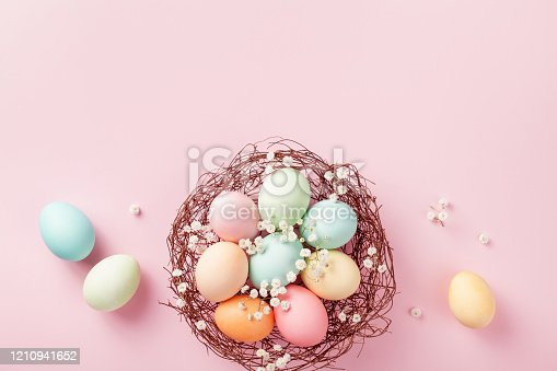 1138213028 istock photo Pastel Easter eggs in nest on pink background top view. Flat lay in modern and fashion style. 1210941652
