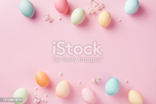 1138213028 istock photo Pastel Easter eggs on pink background top view. Modern flat lay style. 1210941610