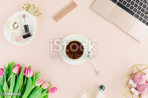 Pastel female office desk table with laptop and cup of coffee. Top view, flat lay.