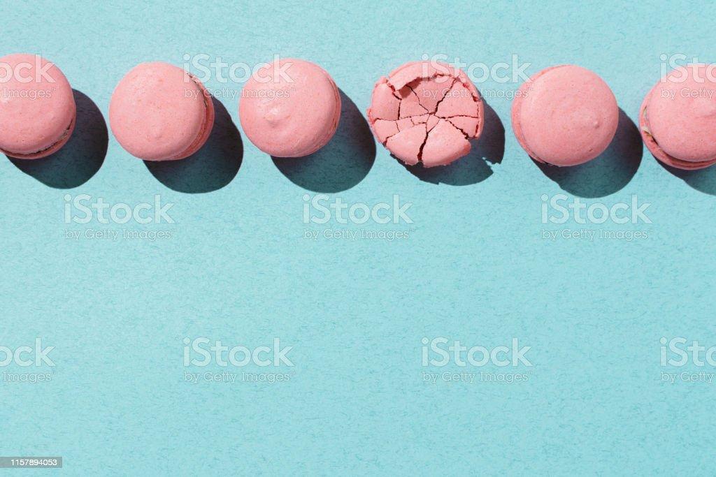 Pastel flatlay of pink vegan macaroons on pastel blue background